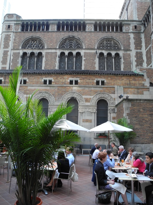 a cafe on the church terrace with palm trees and umbrellas