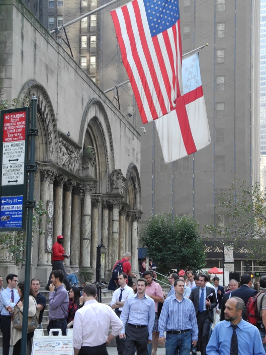 front doors and flags of saint bartholomew's church with a midtown crowd