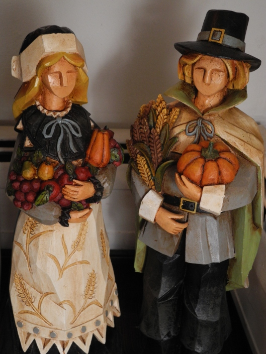 male and female pilgrim statues carrying fall produce