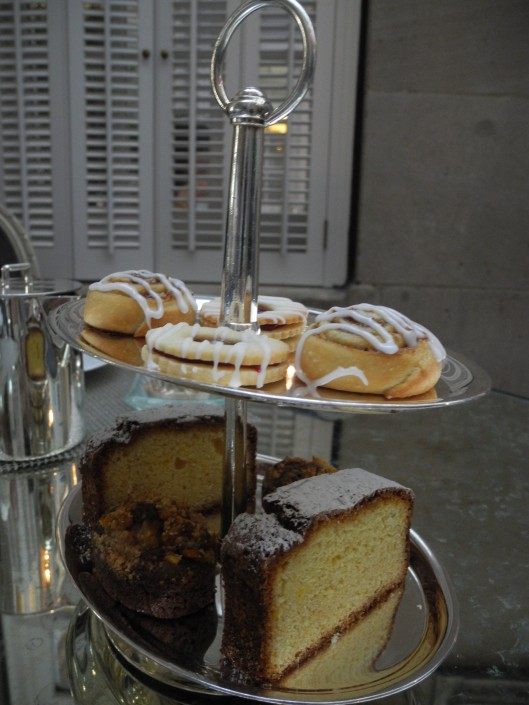 silver tiered tray of cak, cookies and buns