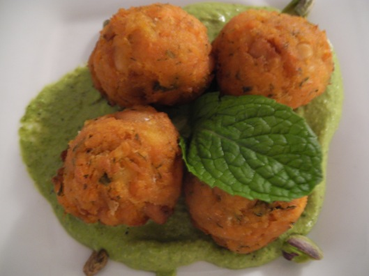 4 carrot balls in a green sauce